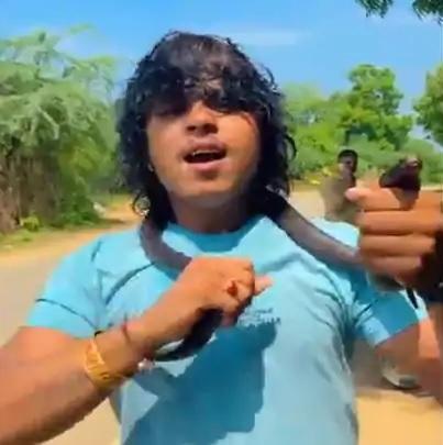 A singer in North Gujarat wraps Cobra snake around neck to shoot video